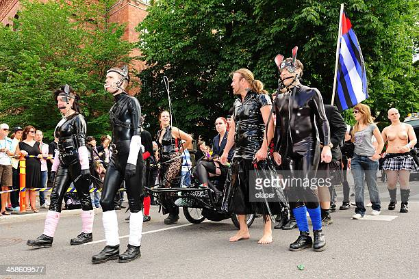 stockholm pride festival - women whipping men stock photos and pictures