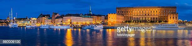 stockholm royal palace ferries gamla stan waterfront illuminated panorama sweden - the stockholm palace stock pictures, royalty-free photos & images