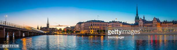 stockholm spires and waterfront restaurants gamla stan illuminated sunset sweden - stockholm bildbanksfoton och bilder