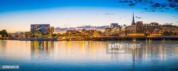 stockholm sunset over norrmalm harbour waterfront illuminated cityscape panorama sweden - waterkant stockfoto's en -beelden