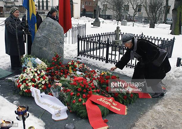 A woman lays a flower on the grave of former Swedish Prime Minister Olof Palme 28 February 2006 The grave is in Adolf Fredrik church cemetery in...