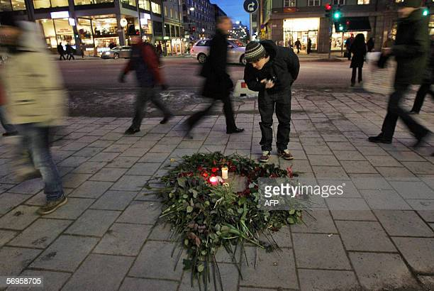 A young man bends over a bunch of roses and lit candles 28 February 2006 on the Stockholm pavement where Swedish Premier Olof Palme was gunned down...