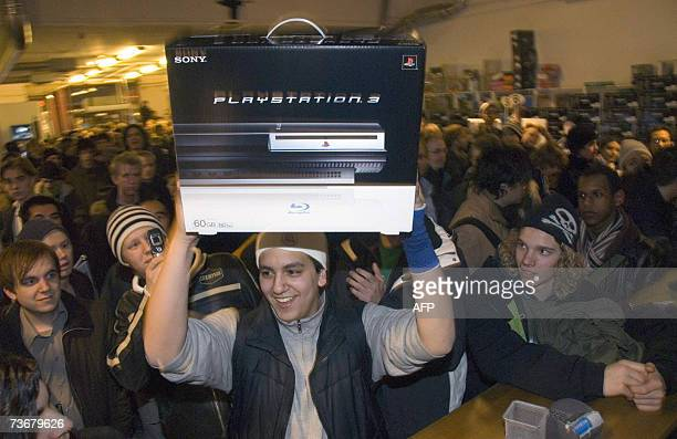 Arash Nahjavi holds up his Playstation 3 after the console was released at the Webhallen store in Stockholm Sweden 1 minute after midnight 23 March...