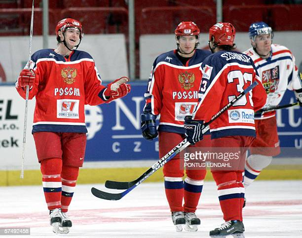 Russia's Ilya Nikulin celebrates with his teammates Maxim Sushinin and Alexander Kharitonov after scoring 7-4 to Russia against Czech Republuc during...