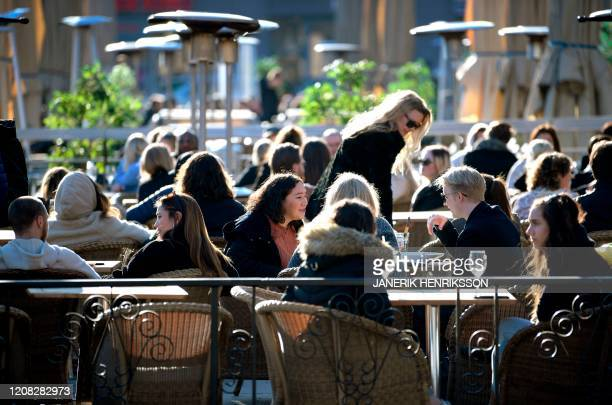 Stockholmers enjoy the sun at a terrace on a square in central Stockholm on March 26 2020 amid the novel coronavirus pandemic / Sweden OUT