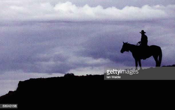 A stockman sits on his horse on a ridge as daylight breaks on the Birdsville Track during the 2005 Great Australian Outback Cattle Drive June 9 near...