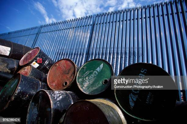 Stockpile of used steel drums in compound
