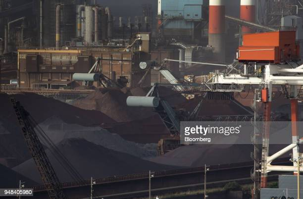 Stockpiles of raw materials including iron ore sit at the Nippon Steel Sumitomo Metal Corp plant in Kashima Ibaraki Japan on Wednesday April 18 2018...