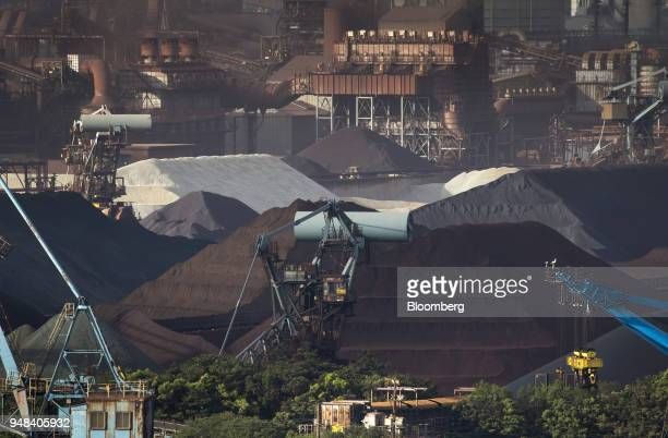 Stockpiles of raw materials including iron ore sit stacked at the Nippon Steel Sumitomo Metal Corp plant in Kashima Ibaraki Japan on Wednesday April...