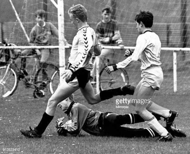Stockton West End keeper Mark Woolnough dives at the feet of Michael Bates to rescue his defence in the North Riding Under 14s Minor Cup Final at...