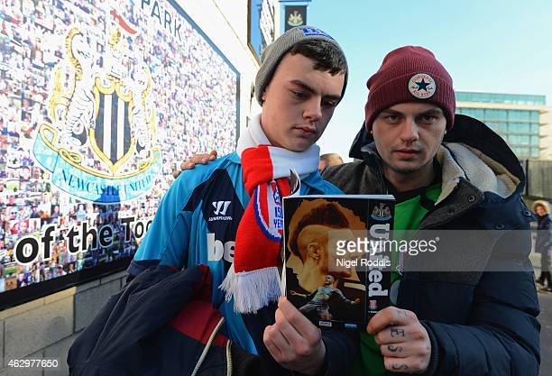 Stoke City fans pose with a programme prior to the Barclays Premier League match between Newcastle United and Stoke City at St James' Park on...