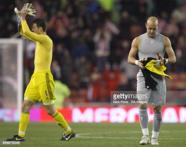 Stoke City goalkeeper Asmir Begovic celebrates as Liverpool goalkeeper Jose Pepe Reina walks off dejected after the final whistle