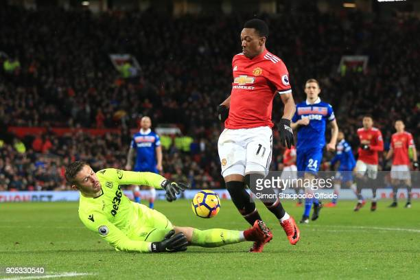 Stoke City goalkeeper Jack Butland slides into Anthony Martial of Manchester United as he makes a save during the Premier League match between...