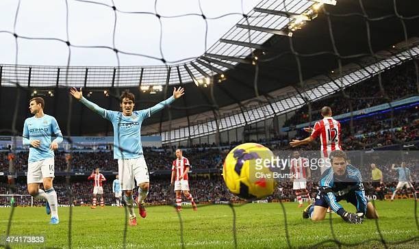 Stoke City keeper Asmir Begovic looks on as David Silva celebrates after team mate Yaya Toure has scored the winning goal during the Barclays Premier...