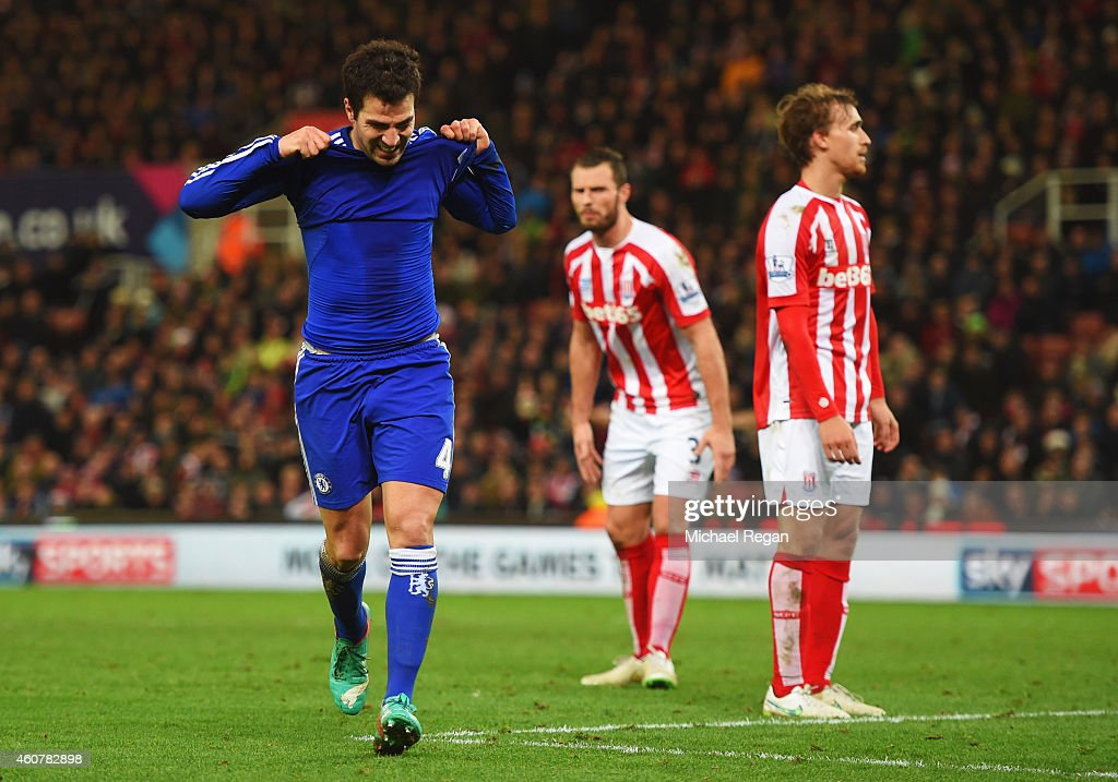 Stoke City players look dejected as Cesc Fabregas of Chelsea celebrates as he scores their second goal during the Barclays Premier League match between Stoke City and Chelsea at Britannia Stadium on December 22, 2014 in Stoke on Trent, England.