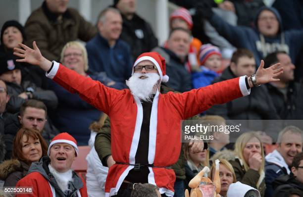 A Stoke City supporter dressed as Father Christmas sings to the United fans during the English Premier League football match between Stoke City and...