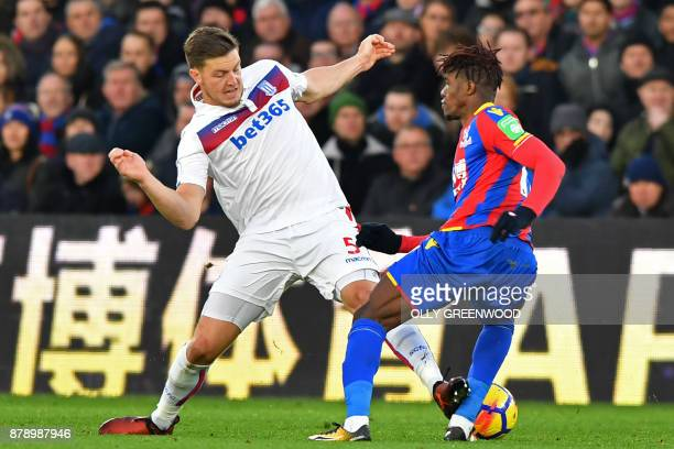 Stoke City's Austrian defender Kevin Wimmer makes a painful challenge on Crystal Palace's Ivorian striker Wilfried Zaha during the English Premier...