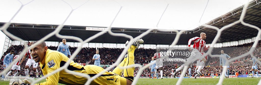 Stoke City's Danny Higginbotham (R) runs to celebrate after scoring a penalty for the opening goal as Tottenham Hotspur's Brazilian goalkeeper Heurelho Gomes (L) looks back to the net during the Premiership football match at The Britannia Stadium in Stoke on October 19, 2008. Stoke won the game 2-1 with Tottenham having two players sent off in the match. AFP PHOTO / Adrian Dennis Mobile and website use of domestic English football pictures are subject to obtaining a Photographic End User Licence from Football DataCo Ltd Tel : +44 (0) 207 864 9121 or e-mail accreditations@football-dataco.com - applies to Premier and Football League matches.