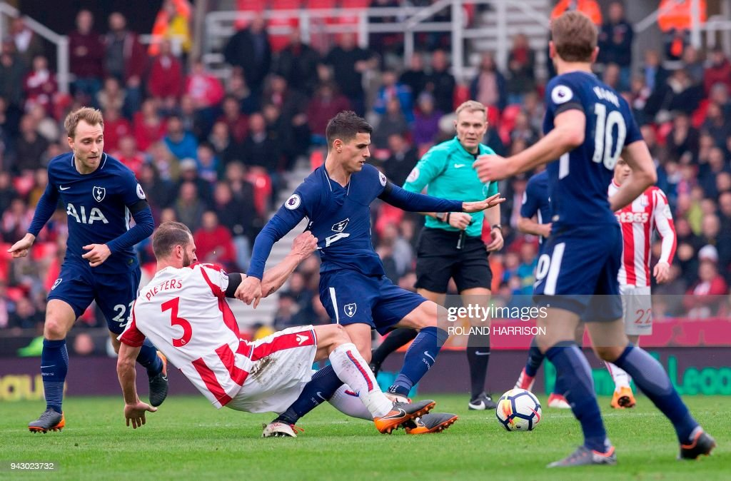 Stoke City's Dutch defender Erik Pieters (2L) fouls Tottenham Hotspur's Argentinian midfielder Erik Lamela (C) during the English Premier League football match between Stoke City and Tottenham Hotspur at the Bet365 Stadium in Stoke-on-Trent, central England on April 7, 2018. / AFP PHOTO / Roland Harrison / RESTRICTED TO EDITORIAL USE. No use with unauthorized audio, video, data, fixture lists, club/league logos or 'live' services. Online in-match use limited to 75 images, no video emulation. No use in betting, games or single club/league/player publications. /