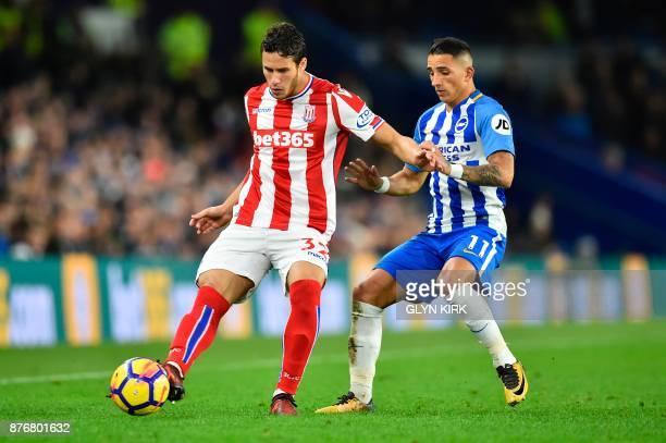 Stoke City's Egyptian midfielder Ramadan Sobhi holds off Brighton's French midfielder Anthony Knockaert to play the ball during the English Premier...