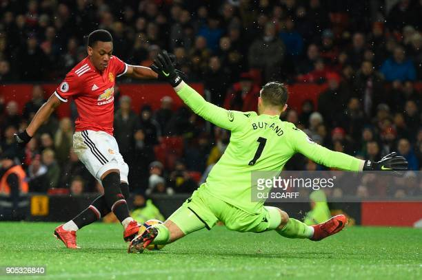 TOPSHOT Stoke City's English goalkeeper Jack Butland beats Manchester United's French striker Anthony Martial to the ball during the English Premier...