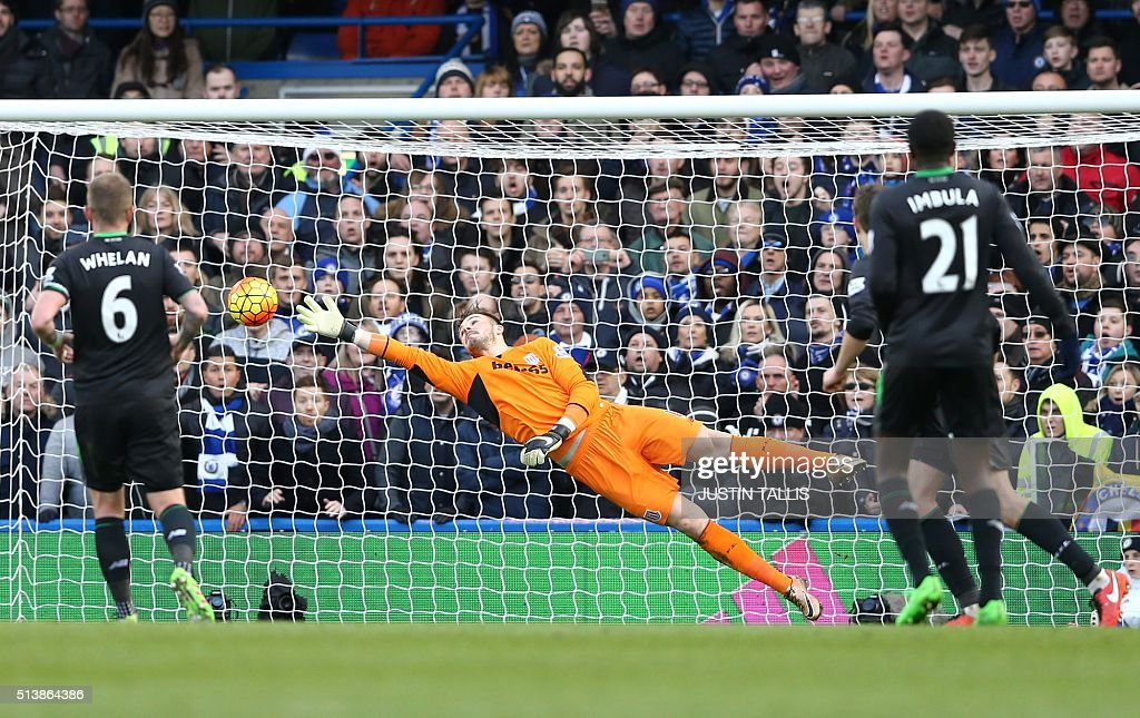 Stoke City's English goalkeeper Jack Butland dives but cannot save the shot from Chelsea's Burkina Faso midfielder Bertrand Traore (not pictured) as Chelsea score the opening goal of the English Premier League football match between Chelsea and Stoke City at Stamford Bridge in London on March 5, 2016. / AFP / JUSTIN TALLIS / RESTRICTED TO EDITORIAL USE. No use with unauthorized audio, video, data, fixture lists, club/league logos or 'live' services. Online in-match use limited to 75 images, no video emulation. No use in betting, games or single club/league/player publications. /