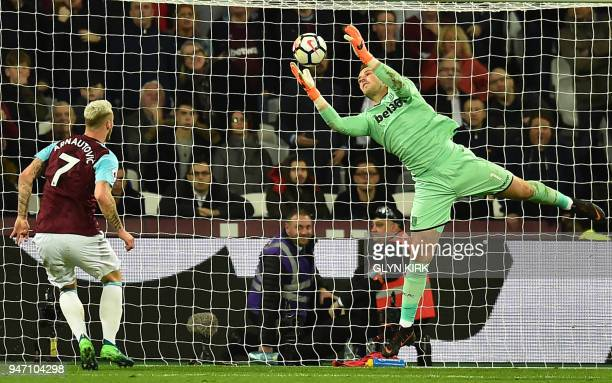 Stoke City's English goalkeeper Jack Butland dives to save a shot from West Ham United's Austrian midfielder Marko Arnautovic during the English...