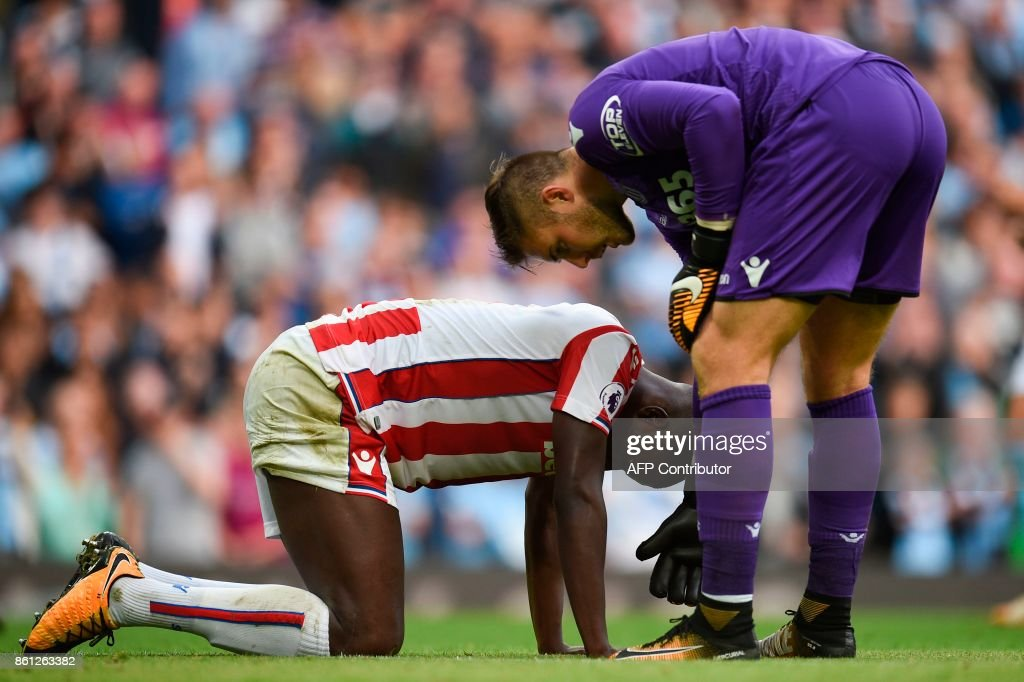 Stoke City's English goalkeeper Jack Butland (R) helps up Stoke City's French defender Kurt Zouma (L) after Machester City's seventh goal during the English Premier League football match between Manchester City and Stoke City at the Etihad Stadium in Manchester, north west England, on October 14, 2017. / AFP PHOTO / Oli SCARFF / RESTRICTED TO EDITORIAL USE. No use with unauthorized audio, video, data, fixture lists, club/league logos or 'live' services. Online in-match use limited to 75 images, no video emulation. No use in betting, games or single club/league/player publications. /