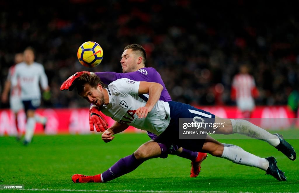 Stoke City's English goalkeeper Jack Butland manages to prevent Tottenham Hotspur's English striker Harry Kane scoring during the English Premier League football match between Tottenham Hotspur and Stoke City at Wembley Stadium in London, on December 9, 2017. / AFP PHOTO / Adrian DENNIS / RESTRICTED TO EDITORIAL USE. No use with unauthorized audio, video, data, fixture lists, club/league logos or 'live' services. Online in-match use limited to 75 images, no video emulation. No use in betting, games or single club/league/player publications. /