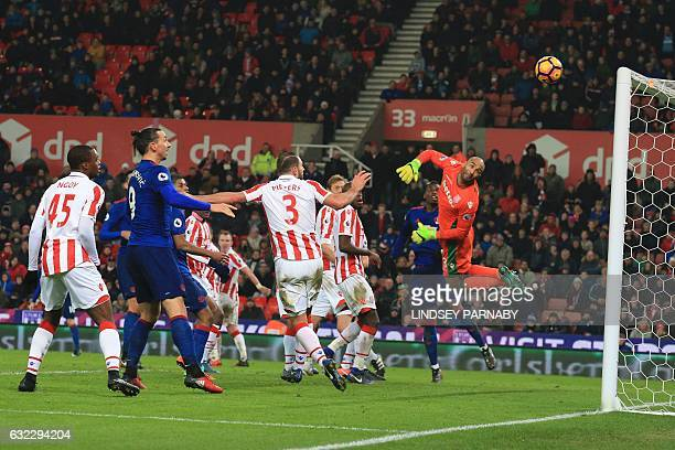 Stoke City's English goalkeeper Lee Grant looks back as he dives to see the ball go into his goal from a free kick hit by Manchester United's English...