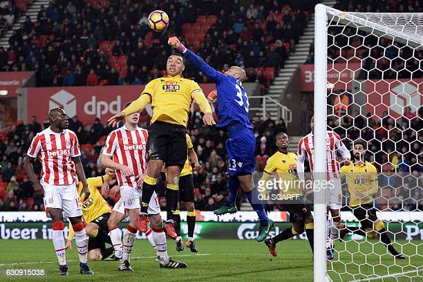Stoke City's English goalkeeper Lee Grant punches clear under pressure from Watford's Englsih striker Troy Deeney during the English Premier League...
