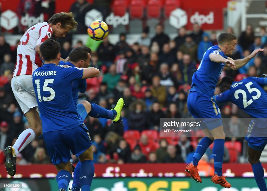 Stoke City's English striker Peter Crouch (L) climbs to head home their second goal during the English Premier League football match between Stoke City and Leicester City at the Bet365 Stadium in Stoke-on-Trent, central England on November 4, 2017. / AFP PHOTO / Paul ELLIS / RESTRICTED TO EDITORIAL USE. No use with unauthorized audio, video, data, fixture lists, club/league logos or 'live' services. Online in-match use limited to 75 images, no video emulation. No use in betting, games or single club/league/player publications. /