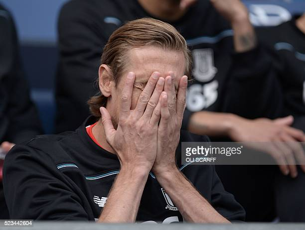 Stoke City's English striker Peter Crouch gestures on the bench ahead of the English Premier League football match between Manchester City and Stoke...