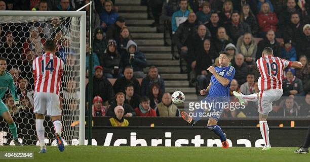 Stoke City's Englishborn Irish striker Jonathan Walters shoots past Chelsea's English defender Gary Cahill to score his team's first goal during the...