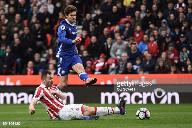 Stoke City's Englishborn Scottish defender Phil Bardsley tries to block a shot by Chelsea's Spanish defender Marcos Alonso during the English Premier...