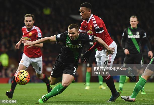 Stoke City's Englishborn Scottish defender Phil Bardsley vies with Manchester United's French striker Anthony Martial during the English Premier...
