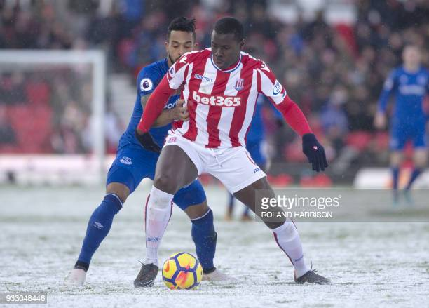Stoke City's French defender Kurt Zouma is challenged by Everton's English striker Theo Walcott during the English Premier League football match...