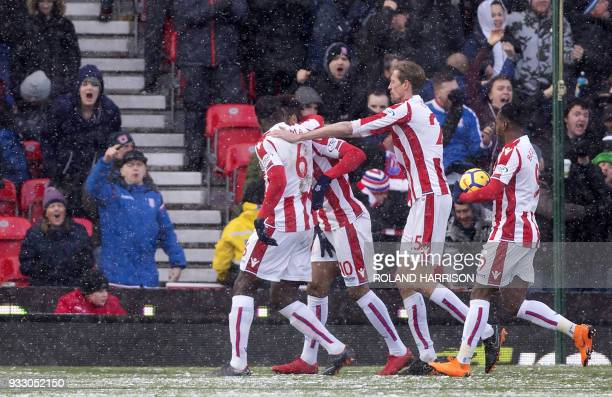 Stoke City's German midfielder Eric Maxim ChoupoMoting celebrates with teammates scoring the team's first goal during the English Premier League...