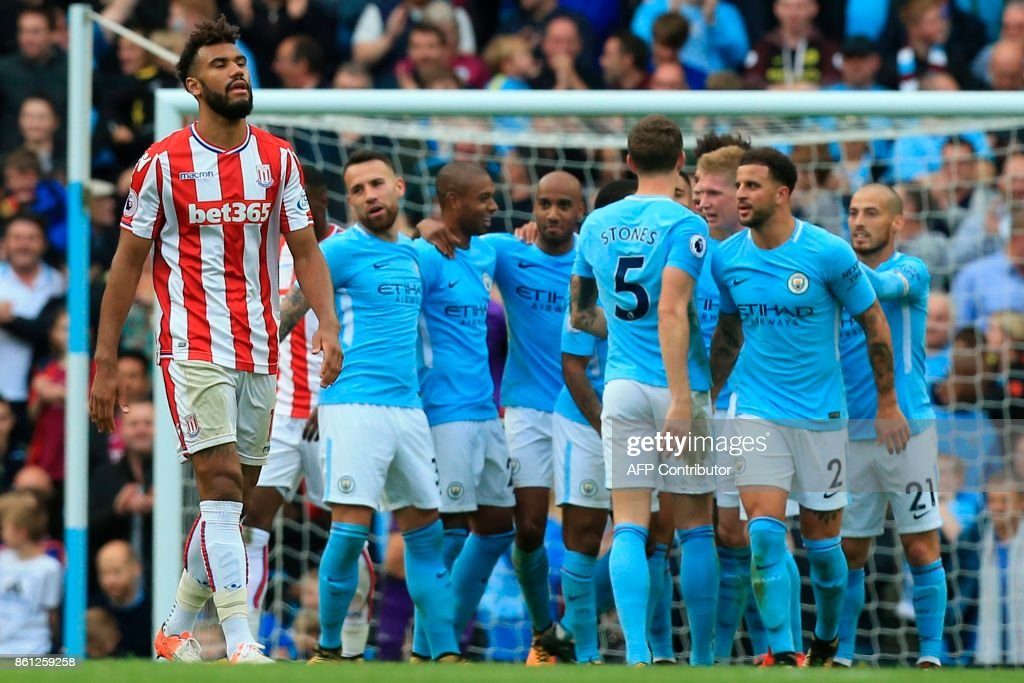 Stoke City's German midfielder Eric Maxim Choupo-Moting (L) reacts as Manchester City players celebrate their sixth goal during the English Premier League football match between Manchester City and Stoke City at the Etihad Stadium in Manchester, north west England, on October 14, 2017. / AFP PHOTO / Lindsey PARNABY / RESTRICTED TO EDITORIAL USE. No use with unauthorized audio, video, data, fixture lists, club/league logos or 'live' services. Online in-match use limited to 75 images, no video emulation. No use in betting, games or single club/league/player publications. /