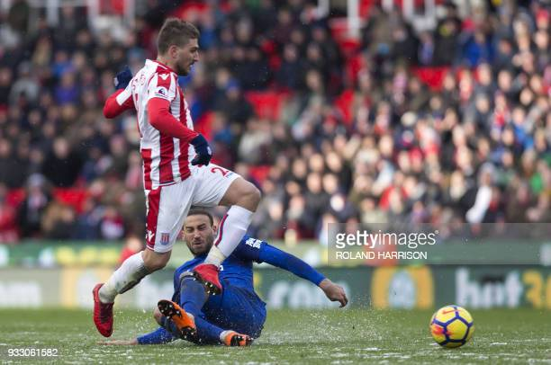 Stoke City's Greek defender Konstantinos Stafylidis vies with Everton's Turkish striker Cenk Tosun during the English Premier League football match...