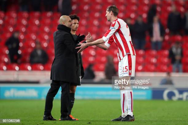 Stoke City's Peter Crouch speaks with Manchester City manager Pep Guardiola and Leroy Sane after the Premier League match at the bet365 Stadium Stoke