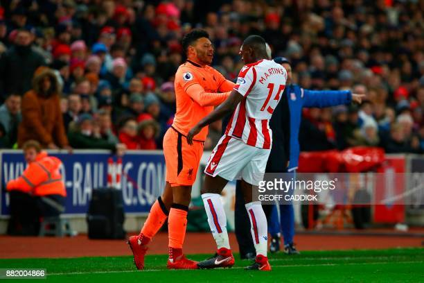 Stoke City's Portugueseborn Dutch defender Bruno Martins Indi clashes with Liverpool's English midfielder Alex OxladeChamberlain during the English...