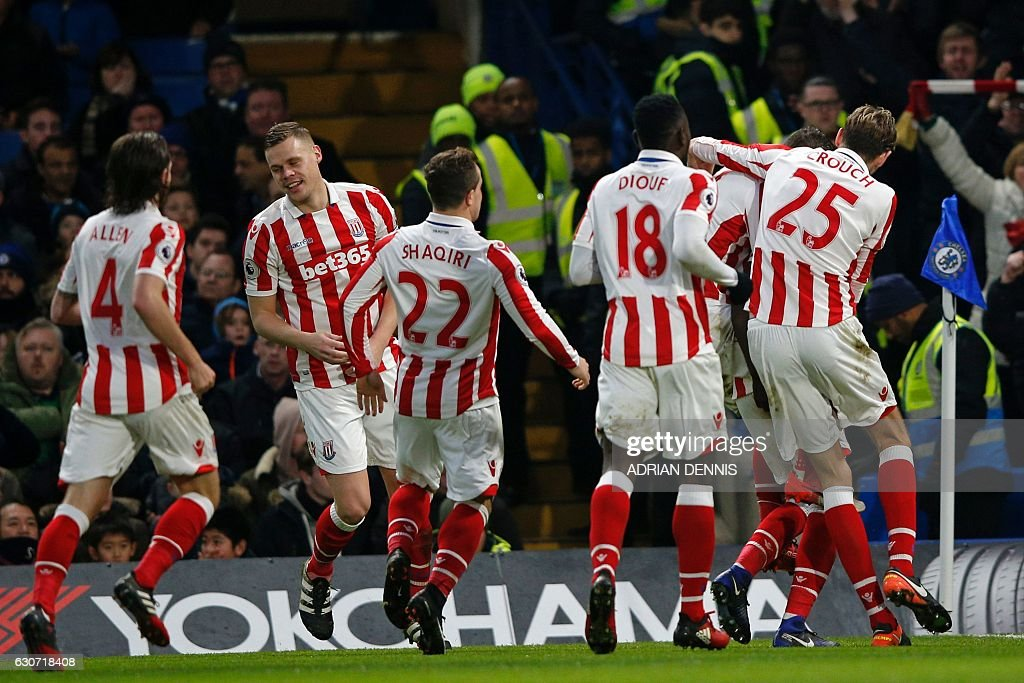 Stoke City's Portuguese-born Dutch defender Bruno Martins Indi celebrates with teammates after scoring their first goal during the English Premier League football match between Chelsea and Stoke City at Stamford Bridge in London on December 31, 2016. / AFP / Adrian DENNIS / RESTRICTED TO EDITORIAL USE. No use with unauthorized audio, video, data, fixture lists, club/league logos or 'live' services. Online in-match use limited to 75 images, no video emulation. No use in betting, games or single club/league/player publications. /