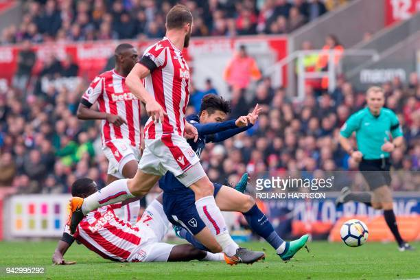 Stoke City's Senegalese defender Badou Ndiaye slide tackles Tottenham Hotspur's South Korean striker Son HeungMin during the English Premier League...