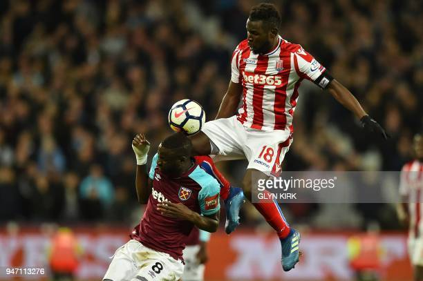 TOPSHOT Stoke City's Senegalese striker Mame Biram Diouf clashes with West Ham United's Senegalese midfielder Cheikhou Kouyate during the English...