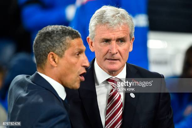 Stoke City's Welsh manager Mark Hughes greets Brighton's Irish manager Chris Hughton for the English Premier League football match between Brighton...