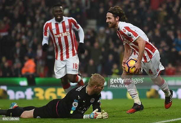 Stoke City's Welsh midfielder Joe Allen carries the ball as he passes Leicester City's Danish goalkeeper Kasper Schmeichel whilst he celebrates...