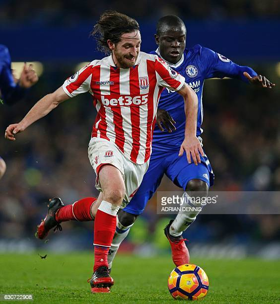 Stoke City's Welsh midfielder Joe Allen runs with the ball as Chelsea's French midfielder N'Golo Kante closes in during the English Premier League...