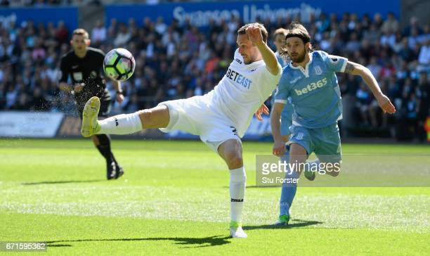 Stoke player Joe Allen challenges Gylfi Sigurdsson of Swansea during the Premier League match between Swansea City and Stoke City at Liberty Stadium...