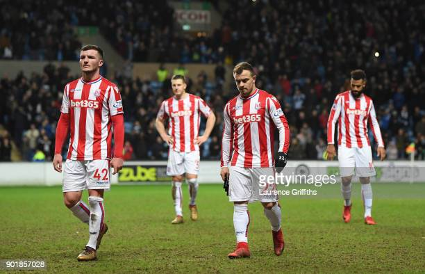 Stoke players Thomas Edwards and Xherdan Shaqiri and dejected team mates leave the field after the The Emirates FA Cup Third Round match between...